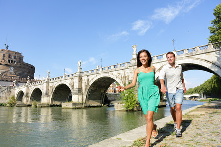 happy asian couple: Romantic couple tourists walking Castel Sant Angelo, Rome. Happy romantic couple looking at the roman castle enjoying their romantic summer holiday travel in Italy, Europe. Man and woman holding hands