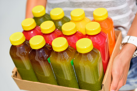 cold drinks: Organic cold-pressed raw vegetable juice plastic bottles. Latest food trend consisting of juicing at high pressure fresh fruits and vegetables without heating to preserve nutrients and vitamins.