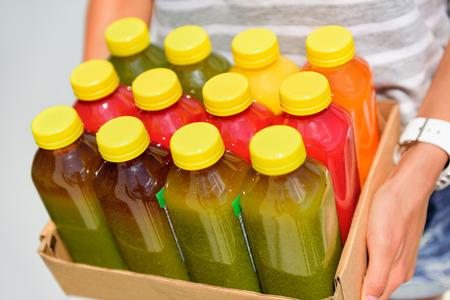jugo de frutas: Vegetales crudos botellas de plástico de jugo de prensado en frío-orgánicos. Las últimas tendencias de alimentos que consiste en extraer el jugo a alta presión frutas y vegetales frescos sin calentar para preservar los nutrientes y vitaminas. Foto de archivo