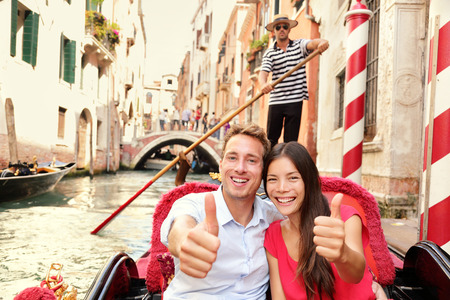 two thumbs up: Tourists happy couple traveling in Venice gondola giving thumbs up hand sign joyful on travel. Romantic young beautiful couple on vacation holidays sailing in venetian canal in gondole. Italy