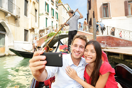 Selfie couple taking picture in gondola on Venice travel vacation. Beautiful lovers on a romantic boat ride across the Venetian canals taking self-portrait pictures with smartphone during holiday.