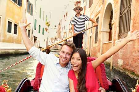 sailing: Tourists on travel happy couple in Venice gondola cheering excited joyful on travel. Romantic young beautiful couple on vacation holidays sailing in venetian canal in gondole. Italy. Asian woman. Stock Photo