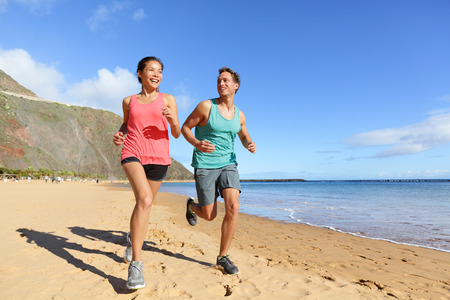 healthy living: Runners running on beach. Jogging couple training on beach in full body length living healthy active lifestyle. Asian runner woman and fit male fitness athlete on run. Stock Photo