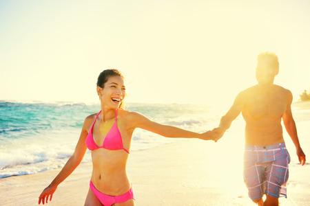 Lachende glückliche romantisches Paar Sommerurlaub beach fun. Joyful multiethnischen junge Paar lachend auf tropischen Strandurlaub auf resort zusammen beschwingt. Mischlinge asiatischen Frau und Mann kaukasischen.
