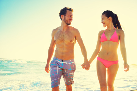 beachwear: Honeymoon couple romantic in love holding hands at beach sunset. Newlywed happy young couple enjoying ocean sunset during travel holidays vacation getaway. Interracial couple.