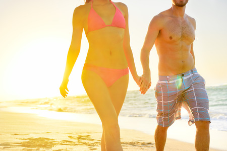 bikini couple: Summer beach couple romantic holding hands at sunset walking in love on honeymoon travel vacation holidays. Unrecognizable woman and man in happy romance wearing bikini and casual beachwear shorts.