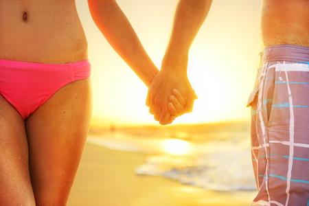 beachwear: Beach sunset couple in love holding hands romantic on honeymoon. Bikini girl and casual beachwear man newlyweds people standing on travel summer vacations on tropical beach. Stock Photo