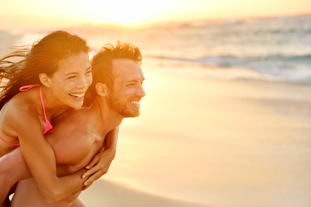 hawaii sunset: Lovers couple in love having fun piggybacking on date on beach. Portrait beautiful healthy young adults girlfriend and boyfriend hugging happy. Multiracial dating or healthy relationship. From Hawaii.