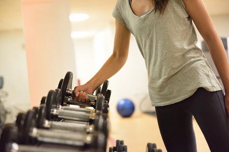 levantar pesas: Mujer Gimnasio pesas con mancuernas elevación entrenamiento de la fuerza que se preparan para el entrenamiento de ejercicio. Muchacha de la aptitud Mujer ejercicio bajo techo en el gimnasio. Hermosa modelo caucásica ajuste raza mixta asiática.