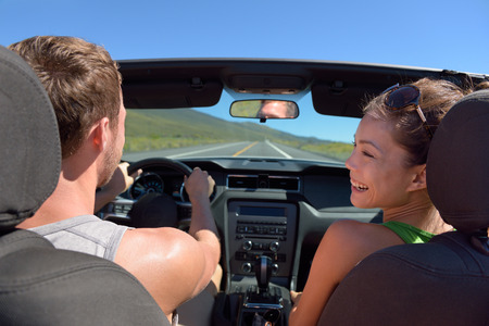 drivers seat: Couple driving car on road trip travel vacation in convertible. Young romantic couple on travel holidays vacation. Man driver behind steering wheel.