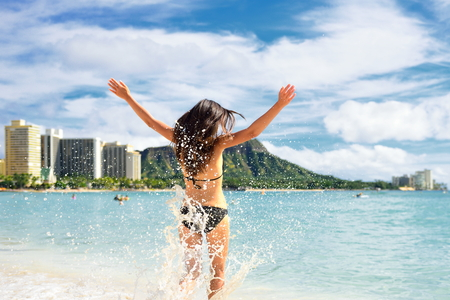 Beach fun - happy woman on Hawaii Waikiki vacation. Unrecognizable young adult from behind jumping of joy in water waves, arms up with diamond head mountain , landmark of Honolulu.