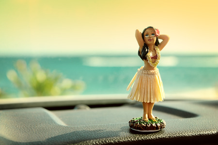 trips: Hula dancer doll on Hawaii car road trip. Doll dancing on the dashboard in front of the ocean. Tourism and Hawaiian travel freedom concept. Stock Photo