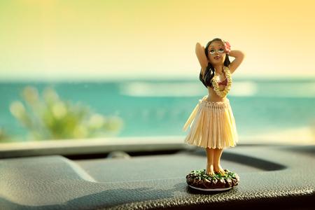 Hula Tänzer Puppe auf Hawaii Auto-Autoreise. Puppe tanzen auf dem Armaturenbrett vor dem Ozean. Tourismus und Hawaiian Reisefreiheit Konzept.