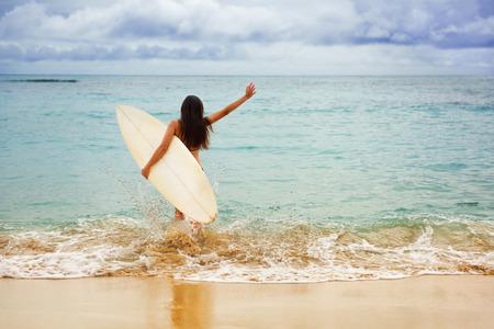 Surfer girl gai et heureux d'aller le surf à Ocean Beach courir dans l'eau. Bikini Femme femme en direction de vagues avec planche de surf amusant vivant mode de vie sain et actif par voie maritime.