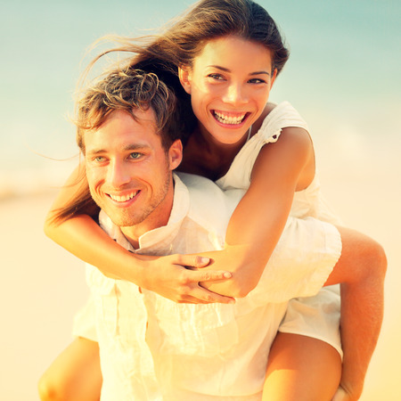 Romantic couple having fun piggyback on beach on honeymoon travel vacation summer holidays romance. Young happy lovers, Asian woman and Caucasian man doing playful joyful piggybacking ride outdoors. Banco de Imagens