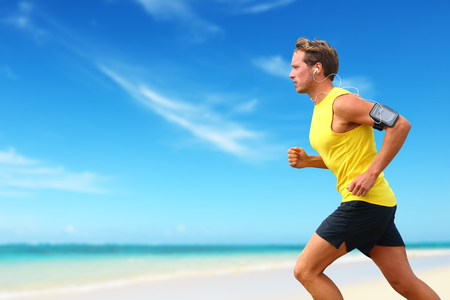 smartphone: Runner running listening smartphone music on beach cardio workout. Male athlete jogging on ocean beach or waterfront working out with smart phone app device and earphones in summer.