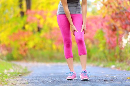 muslos: Lesión muscular del muslo femenino corredor deportes. Mujer que se ejecuta lesiones por esfuerzo muscular en el muslo. Primer plano de corredor tocando la pierna en el dolor muscular fuera en el bosque de otoño.