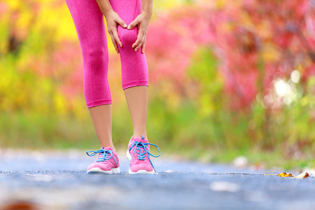 physical injury: Knee Injury - running sport knee injuries on woman. Female runner with pain from sprain knee. Close up of legs, muscle and knee outdoors in forest. Stock Photo