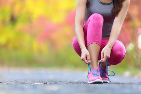 hacer footing: El calzado para correr - mujer atar cordones de los zapatos. Primer plano de corredor de fitness deporte femenino preparándose para correr al aire libre en la pista forestal a finales del verano o el otoño. Foto de archivo