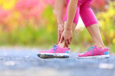 Running sport injury - twisted broken ankle. Female athlete runner touching foot in pain due to sprained ankle. Stock Photo - 40349906