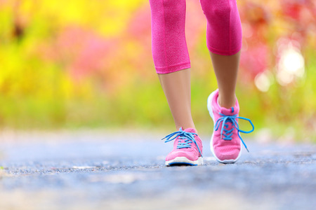 La marche et le jogging femme aux jambes athlétiques et chaussures de course. Femme marche sur le sentier en forêt dans le concept de mode de vie sain avec gros plan sur les chaussures de course. Femme formation jogger de l'athlète à l'extérieur.