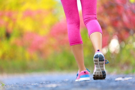 trails: Jogging and running woman with athletic legs on jog or run on trail in forest in healthy lifestyle concept with close up on running shoes. Female athlete jogging and training outdoors in autumn fall.