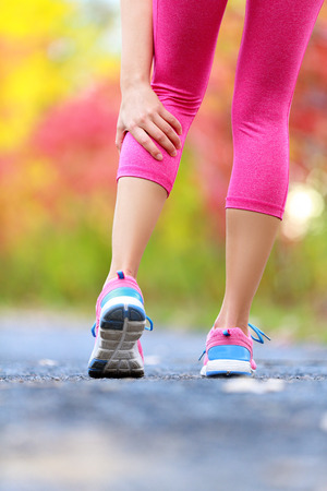 calf strain: Woman running clutching calf muscle injury after spraining it while out jogging on the beach. Female athlete sport injury. Outside on forest path.