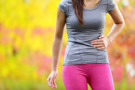 Side cramps - woman runner side stitch after running. Jogging woman with stomach side pain after jogging work out. Female athlete in colorful late summer autumn forest. Stok Fotoğraf - 40349946