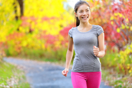 cross walk: Woman power walking nordic speed walk and jogging and running lightly in forest in spring or summer. Sport fitness girl sports training and working out living healthy active lifestyle in forest. Stock Photo