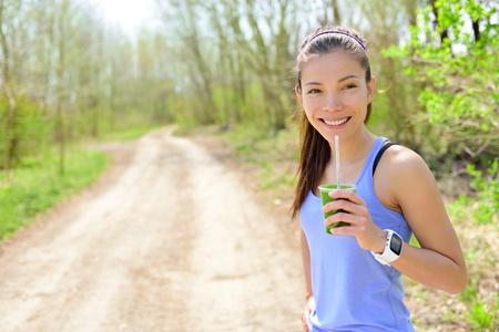 heart monitor: Healthy woman drinking green smoothie wearing smartwatch. Female runner resting drinking a spinach and vegetable smoothie using smart watch heart rate monitor during outdoor running workout in forest.