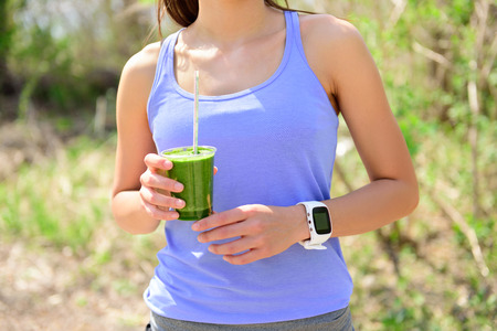 cleanse: Green smoothie - woman runner wearing smartwatch. Healthy woman drinking vegetable smoothie wearing smart watch heart rate monitor during outdoor running workout in forest. Stock Photo