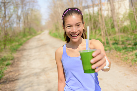 green vegetable: Green vegetable smoothie - healthy lifestyle and eating concept. Close up of green vegetable detox smoothie with spinach. Woman hand holding vegetable smoothies outdoors in forest.