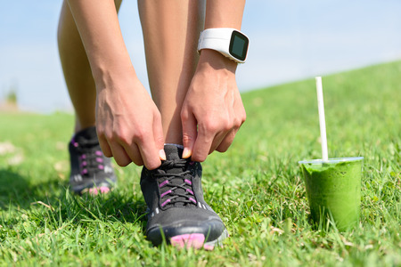 watch city: Running shoes, sports smartwatch and green smoothie. Female runner tying shoe laces in city park while drinking a healthy spinach and vegetable smoothie using smart watch heart rate monitor.
