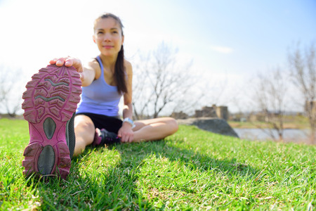 Fit fitness woman doing stretching exercises outdoors on grass. Girl doing hamstring leg stretching exercise and stretches. Female sports model exercising outdoor in summer. Beautiful Asian girl. 스톡 콘텐츠