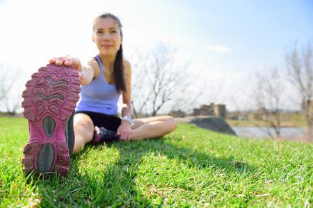 Fit fitness vrouw doen rekoefeningen buiten op gras. Meisje doet hamstring been stretching oefening en strekt. Vrouwelijk sportmodel uitoefening van buiten in de zomer. Mooi Aziatisch meisje.