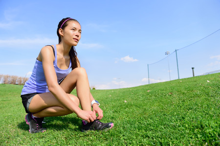 early summer: Young sporty woman runner preparing for run in morning in the beautiful nature. Wellness and healthy lifestyle concept with mixed race Asian Caucasian female model going running.