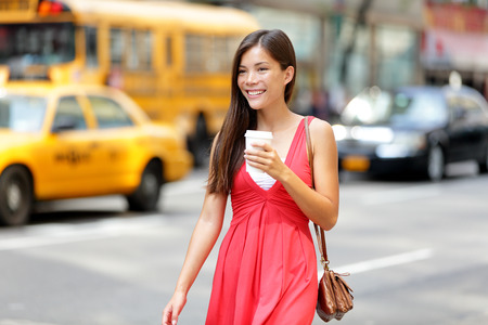 Urban woman drinking coffee happy smiling in New York City, Manhattan. Girl drinking hot drink from disposable cup walking in street wearing red dress. Biracial Asian Caucasian female model. Stock Photo