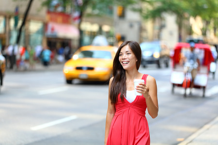taxi: Casual young urban woman drinking coffee happy smiling in New York City, Manhattan. Girl drinking hot drink from disposable cup walking in street wearing red dress with yellow taxi cabs .