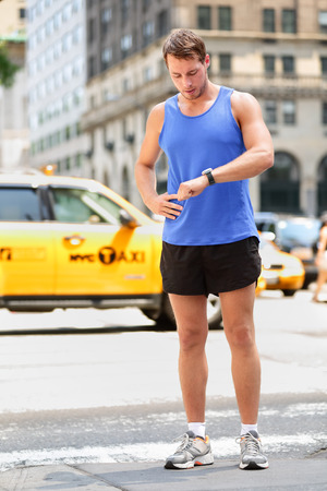 heart rate monitor: Runner looking at smartwatch heart rate monitor having break while running in New York City, Manhattan. Man jogging outside looking at sports smart watch training for marathon. Male fitness model Stock Photo