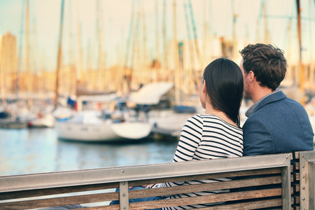 Lovers couple Romantic dating sitting on bench on date in old harbour, Port Vell, Barcelona, Catalonia, Spain. Happy woman and man embracing enjoying life and romance outside Stockfoto
