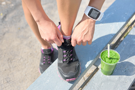 Running shoes, green vegetable smoothie and sports smartwatch. Female runner tying shoe laces in city park while drinking a healthy spinach and vegetable smoothie using smart watch heart rate monitor.