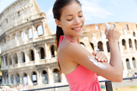 uv: Woman applying sunscreen suntan lotion on travel in Rome by the Colosseum. Beautiful happy woman Asian putting solar cream from a plastic container in Italy while enjoying Europe summer traveling. Stock Photo