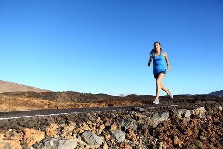 razas de personas: Mujer corriente - femenino trotar corredor al aire libre en la formaci�n de ruta para la corrida del marat�n como parte del entrenamiento al aire libre estilo de vida saludable en verano. Raza mixta modelo cauc�sico asi�tico.