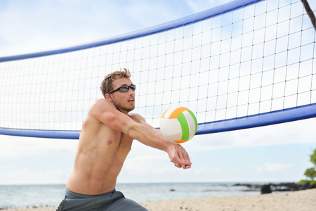 young male: Beach volleyball man playing game hitting forearm pass volley ball during match on summer beach. Male model living healthy active lifestyle doing sport on beach. Stock Photo
