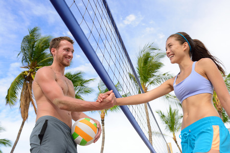female volleyball: Handshake people in beach volleyball shaking hands after volley ball game on summer beach. Man and woman model living healthy active fitness lifestyle doing sport on beach. Stock Photo