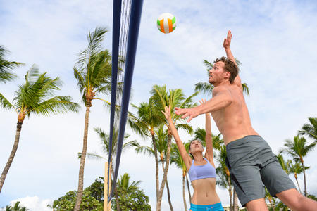 female volleyball: Friends playing beach volleyball sport in summer. Woman volley the ball to man jumping to smash. People having fun recreational volley ball game living healthy active sport lifestyle.
