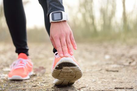 Finaliste étirement jambe avant terme. Gros plan de chaussures de course d'un orteil touchante jogger femme portant une technologie portable - activité sportive exprime Tracker ou Smartwatch utilisé comme un moniteur de fréquence cardiaque pour le cardio. Banque d'images