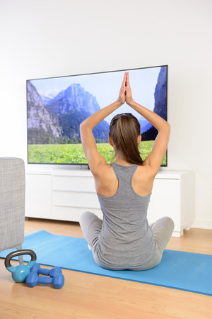 meditation room: Woman doing home yoga meditation in front of TV. Fit girl doing easy pose relaxation exercises watching a TV show or training video with arms raised sitting on the floor of the living room.