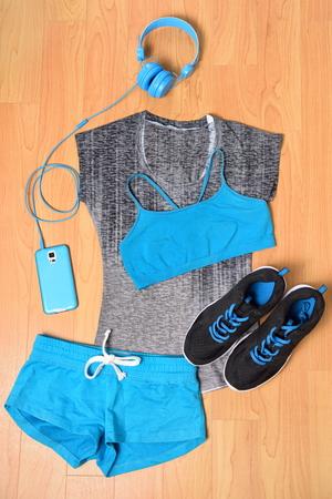 ginástica: Gym outfit - roupas de ginástica, tênis de corrida, fones de ouvido e smartphone para ouvir música enquanto trabalham fora no centro de fitness. Roupas, sutiã esportivo, shorts em azul e preto de harmonização.
