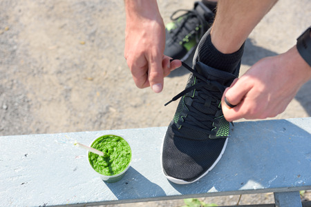 Green smoothie and running - healthy lifestyle. Closeup of male runner's sport shoe tying laces on park bench for diet and weight loss concept for men. Getting ready for jogging and cardio workout.